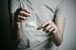 The fight against drugs and drug addiction topic: addict holding package of cocaine in a gray T-shirt on a dark background in the Royalty Free Stock Image