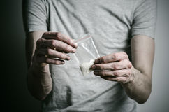 The fight against drugs and drug addiction topic: addict holding package of cocaine in a gray T-shirt on a dark background in the Stock Photo