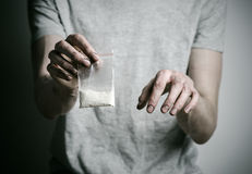 The fight against drugs and drug addiction topic: addict holding package of cocaine in a gray T-shirt on a dark background in the Stock Photography