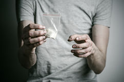 The fight against drugs and drug addiction topic: addict holding package of cocaine in a gray T-shirt on a dark background in the Royalty Free Stock Photos