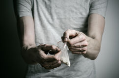 The fight against drugs and drug addiction topic: addict holding package of cocaine in a gray T-shirt on a dark background in the Stock Images