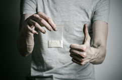 The fight against drugs and drug addiction topic: addict holding package of cocaine in a gray T-shirt on a dark background in the Royalty Free Stock Photography