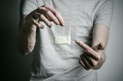 The fight against drugs and drug addiction topic: addict holding package of cocaine in a gray T-shirt on a dark background in the. The fight against drugs and Stock Photography