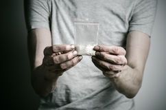 The fight against drugs and drug addiction topic: addict holding package of cocaine in a gray T-shirt on a dark background in the Royalty Free Stock Images