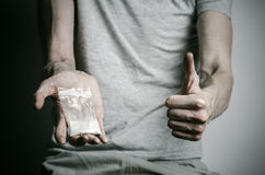 The fight against drugs and drug addiction topic: addict holding package of cocaine in a gray T-shirt on a dark background in the Royalty Free Stock Photo