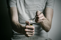 The fight against drugs and drug addiction topic: addict holding spoon lighter and heats the liquid drug in a T-shirt on a dark ba Stock Photos