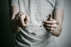 The fight against drugs and drug addiction topic: addict holding spoon lighter and heats the liquid drug in a T-shirt on a dark ba. Ckground in studio Stock Photo