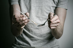 The fight against drugs and drug addiction topic: addict holding spoon lighter and heats the liquid drug in a T-shirt on a dark ba. Ckground in studio Royalty Free Stock Photography