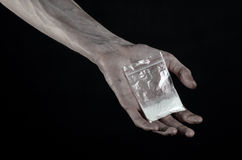 The fight against drugs and drug addiction topic: dirty hand holding a bag addict cocaine on a black background in the studio Royalty Free Stock Photo
