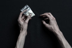 The fight against drugs and drug addiction topic: hand addict lies on a dark table and around it are drugs, a top studio. The fight against drugs and drug Royalty Free Stock Photo