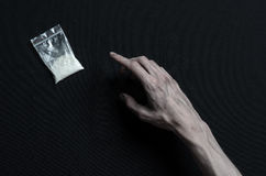 The fight against drugs and drug addiction topic: hand addict lies on a dark table and around it are drugs, a top studio Royalty Free Stock Photo