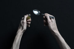 The fight against drugs and drug addiction topic: hand addict lies on a dark table and around it are drugs, a top studio Royalty Free Stock Photos