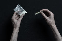 The fight against drugs and drug addiction topic: hand addict lies on a dark table and around it are drugs, a top studio. The fight against drugs and drug Royalty Free Stock Photography