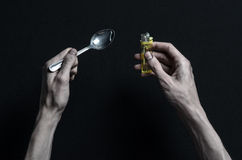 The fight against drugs and drug addiction topic: hand addict lies on a dark table and around it are drugs, a top studio. The fight against drugs and drug stock photography
