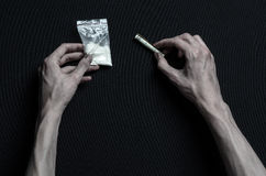 The fight against drugs and drug addiction topic: hand addict lies on a dark table and around it are drugs, a top studio Stock Photo