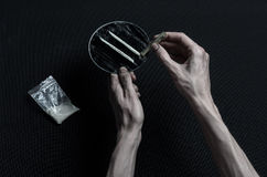 The fight against drugs and drug addiction topic: hand addict lies on a dark table and around it are drugs, a top studio Stock Photos