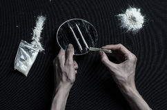 The fight against drugs and drug addiction topic: hand addict lies on a dark table and around it are drugs, a top studio. The fight against drugs and drug royalty free stock images