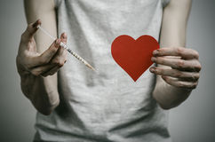 The fight against drugs and drug addiction topic: skinny dirty addict holding a syringe with a drug and red heart on a dark backgr Stock Photos