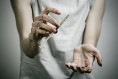 The fight against drugs and drug addiction topic: skinny dirty addict holding a syringe with a drug and red heart on a dark backgr Royalty Free Stock Image
