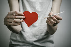 The fight against drugs and drug addiction topic: skinny dirty addict holding a syringe with a drug and red heart on a dark backgr Stock Photography