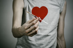 The fight against drugs and drug addiction topic: skinny dirty addict holding a syringe with a drug and red heart on a dark backgr Royalty Free Stock Images