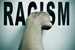 Fight against racism. A man punching the word racism, depicting the concept of the fight against racism royalty free stock photos