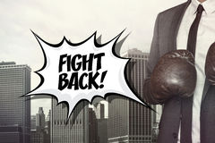 Fight back text with businessman wearing boxing Stock Photos