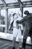 Fight between business partners. Two young businessmen fight at office Stock Images