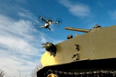 The fight with the drones. Quadcopter near the tank.  stock photo