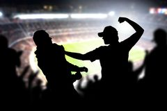 Fight in a football game crowd. Angry man hitting another spectator in soccer match audience. Violent argument between two fans of different teams and clubs royalty free stock photos