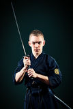 Before the fight. Handsome young man practicing kendo. Over dark background stock photo