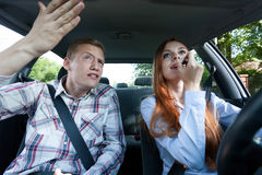 Fight over makeup in car. Young men mad at women for putting on lipstick in car Royalty Free Stock Photo