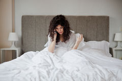 Fight on the phone. Sad woman fight on the phone in the morning from her bed royalty free stock photos