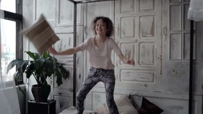 Fight by pillows of man and woman in pajamas. Loving multiethnic couple have fun, carefree morning together. Slow motion stock video