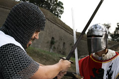 Fight of two knights. Angry face on one who strikes other knight with a sword royalty free stock image