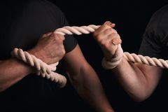 Tug-of-war. Men tighten a rope on a black background. The fight of two men with a tug of war. Tug-of-war Royalty Free Stock Photography