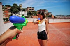 Girl shooting with a water guns. stock image