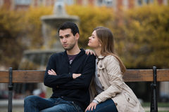 After fight. Young couple having romantic conversation after love fight on the bench in park in Paris, France royalty free stock image