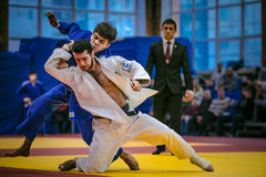 Fight between young male judoists. in background referee Stock Photography
