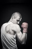 Fighter. Young agressive boxer posing over dark background Royalty Free Stock Photography