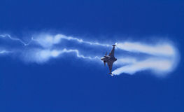 Fighter aircraft zooming past. A fighter trailing smoke makes a low pass in an airshow stock image