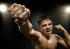 Fighter. Horizontal  photo  muscular young  guy street-fighter, cuff  fist close up on camera and yell , hard light Stock Images