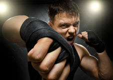 Fighter. Horizontal  photo  muscular young  guy street-fighter, cuff  fist close up on camera and yell , hard light Royalty Free Stock Photos