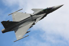 Fighter jet flyby. A Saab Gripen flies close by during airshow, banking right Royalty Free Stock Images