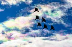 Fighter jet group flies in the clouds and iris multicolored . Fighter jet group flies in the clouds and iris multicolored sky Royalty Free Stock Photo