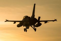 Fighter jet landing at sunset. A fighter jet is ready to land at an airbase during a beautiful sunset Royalty Free Stock Photography