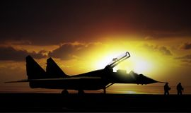 Fighter jet under sunset on super carrier at sea Stock Photos