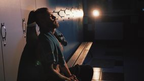 Fighter in the locker room. Tired boxer sitting in locker room at fitness studio stock footage