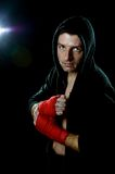 Fighter man in boxing hoodie jumper with hood on head with hand and wrist wrapped ready for fighting posing isolated Royalty Free Stock Photo