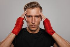 Fighter man concentrating. Adult fighter man with bandage arms looking at camera and concentrating Royalty Free Stock Images